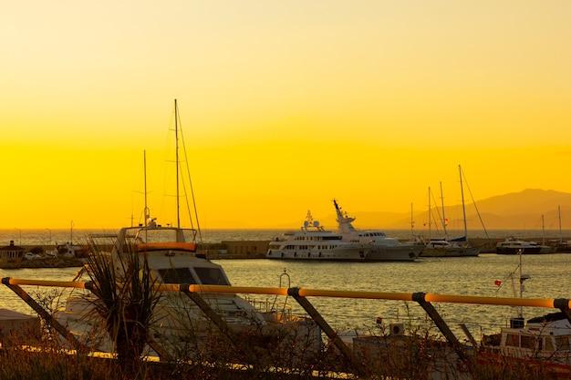 Yates atracados en el puerto marítimo al atardecer. paisaje marino con barcos y montaña. aparcamiento marítimo de lancha a motor