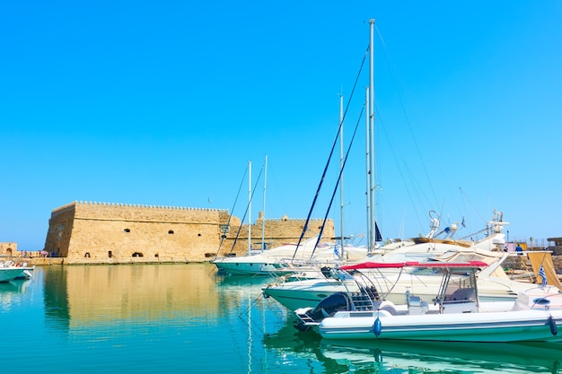 Yates de vela en el puerto de la antigua fortaleza veneciana en heraklion, isla de creta, grecia