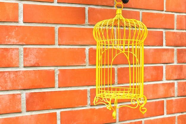Yellow birdcage en el fondo de la pared de ladrillo.