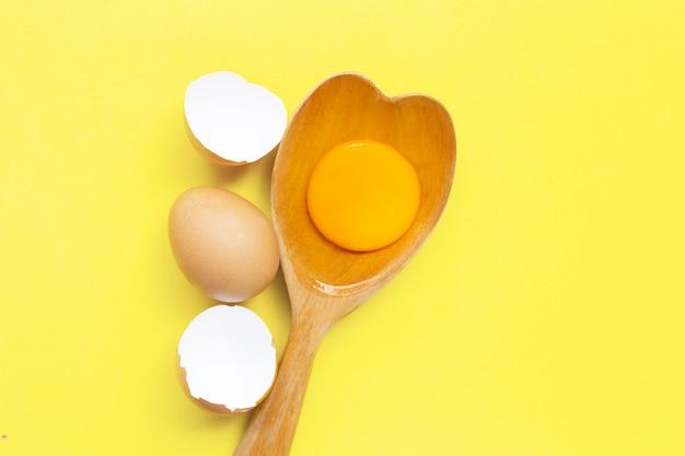 La yema de huevo y el blanco en corazón de madera de la cuchara forman en amarillo.