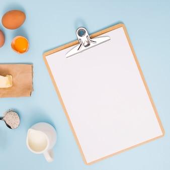 Yema; mantequilla; jarra de harina y leche cerca del libro blanco en el portapapeles de madera sobre fondo azul