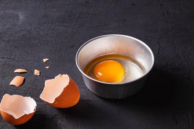 Yemas de huevo y proteínas en una taza. corolla batir los huevos. preparación de alimentos y huevos de gallina.