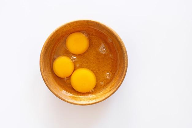 Yemas de huevo en un tazón de madera sobre blanco