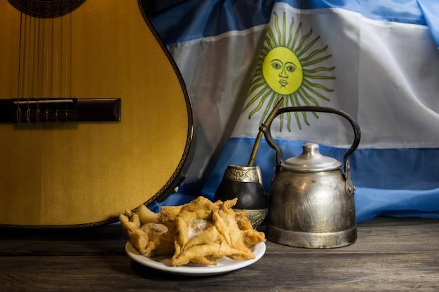 Yerba mate, guitarra y bollería frita con bandera argentina al fondo