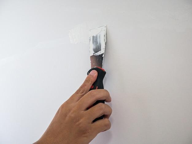 Yesero reparación de la mano crack pared blanca