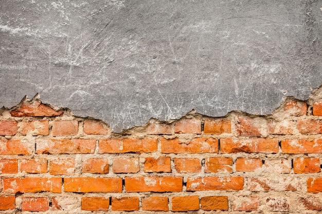 Yeso viejo y dañado en la pared de ladrillo rojo