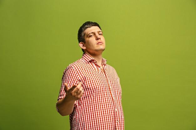 Yo te elijo y hago el pedido. el hombre de negocios sonriente le señala, le quiere, retrato de portarretrato de media longitud sobre fondo verde de estudio.