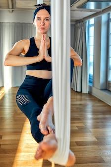 Yoga aéreo una hermosa chica entrenadora de yoga aéreo muestra una variedad de ejercicios en líneas colgantes en una sala de yoga