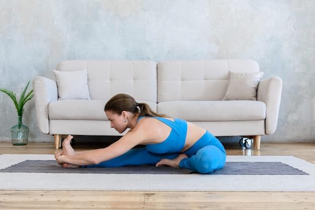 Yoga en casa, mujer yogui entra para ejercicios deportivos de estiramiento en su apartamento