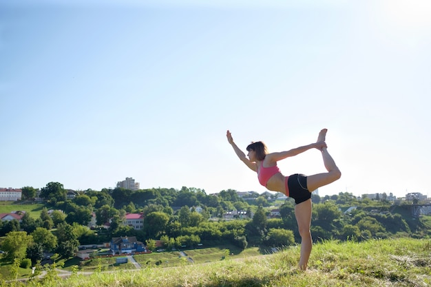 Yoga. día internacional de joga. atractiva mujer en forma practicando yoga al aire libre.