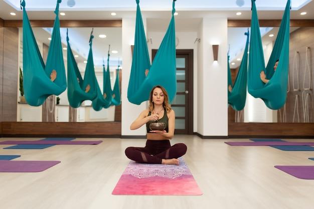 Yoga entrenador con el bolo de meditación introduce a sus pupilos en trance