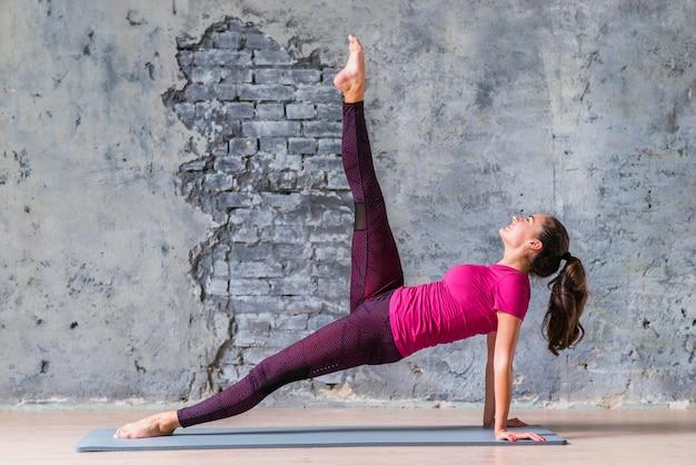 Yoga del entrenamiento de la mujer de la aptitud en la estera del ejercicio contra la pared dañada gris
