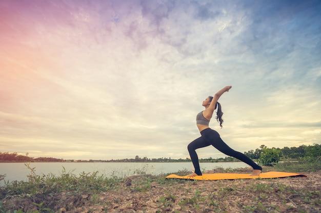 Yoga hermosa de la muchacha en el parque en el cielo hermoso del día soleado.