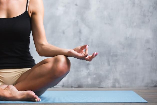 Yoga en interiores. mujer en posición de loto en loft deportivo,