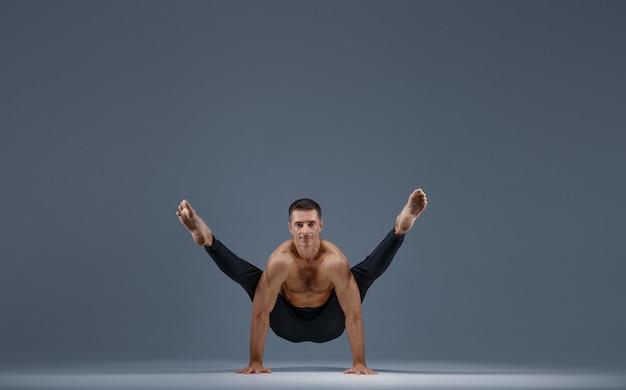Yoga masculino haciendo ejercicios de estiramiento sobre fondo gris. hombre fuerte practicando yogui, entrenamiento de asanas, máxima concentración, estilo de vida saludable