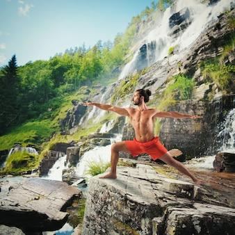 Yoga en un paisaje natural con cascada.