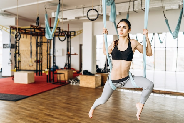 Yoga practicante de la mosca de la muchacha bastante delgada de la aptitud del cuerpo en el gimnasio.