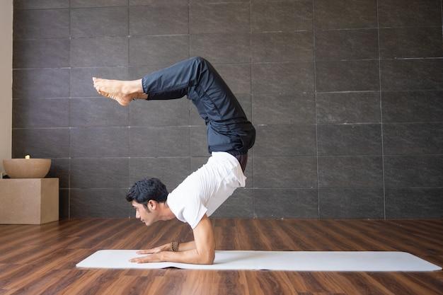 Yogui experimentado haciendo yoga escorpión posa en el gimnasio