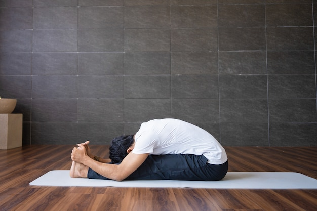 Yogui experimentado haciendo yoga sentada sentada hacia adelante