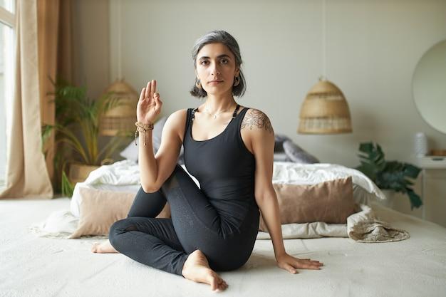 Yogui femenina avanzada joven flexible con canas prematuras sentada en el suelo en postura ardha matsyendrasana, haciendo un giro espinal sentado para mejorar la digestión y aliviar el dolor de espalda