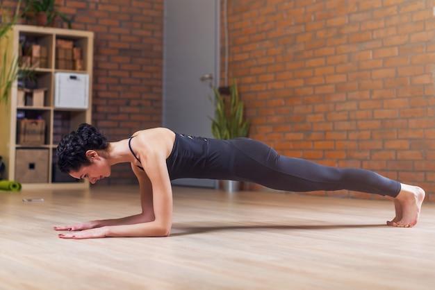 Yogui femenino joven delgado haciendo pose de tabla de pilates en el piso haciendo ejercicio en casa