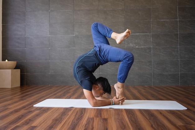 Yogui haciendo mano difícil posición de yoga pose en el gimnasio