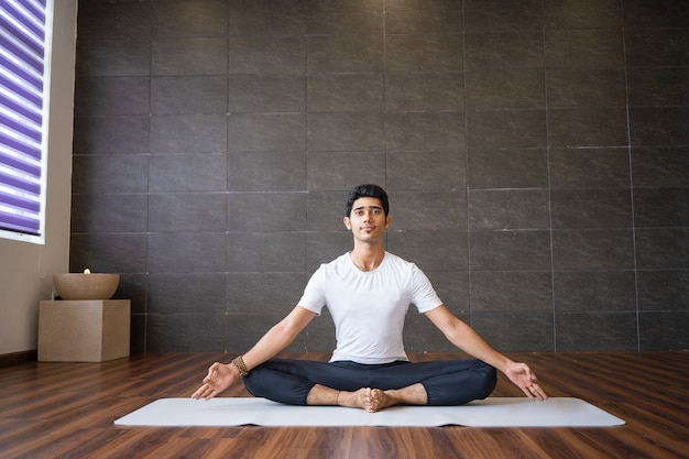 Yogui indio sentado y sosteniendo los pies juntos en el gimnasio