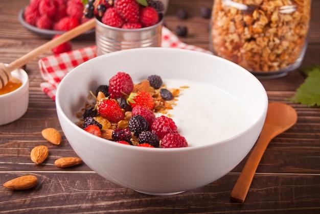 Yogur con bayas frescas, muesli granola de avena en la mesa de madera.