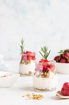 Yogur de bayas con yogur griego, fresas frescas y granola en frascos. desayuno saludable parfait en vaso de vidrio