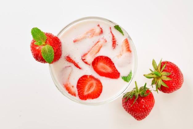 Yogur casero con fresa roja fresca sobre un fondo de madera. vista superior.