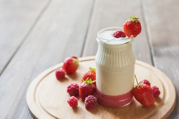 Yogur casero en un primer plano de tarro. producto de leche fermentada con fresas y copia espacio.