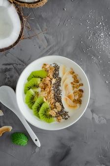 Yogur de coco casero en un tazón de granola, rodajas de kiwi, semillas de chía y crujientes chips de coco. desayuno saludable. comida vegana.