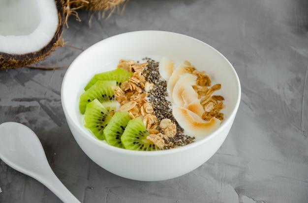 Yogur de coco casero en un tazón de granola, rodajas de kiwi, semillas de chía y crujientes chips de coco. desayuno saludable.