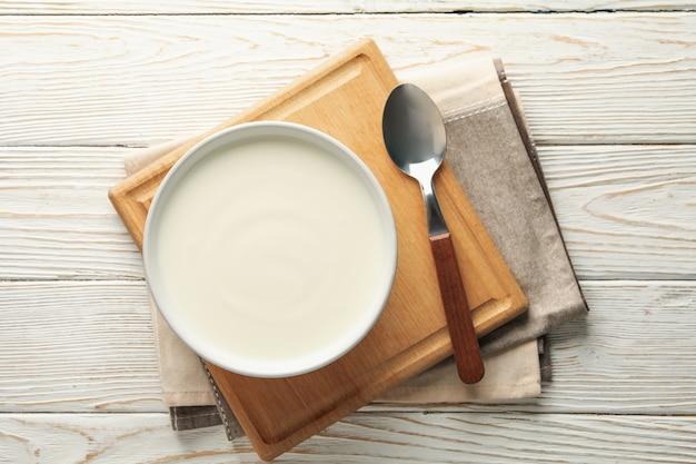 Yogur de crema agria, cucharas y servilletas en madera blanca