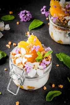 Yogur con granola, naranja, menta y flores comestibles.