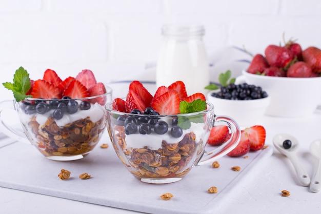 Yogur griego casero con granola, menta, arándanos y fresa en vasos de vidrio sobre fondo blanco, concepto de desayuno saludable