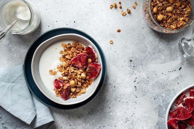 Yogur griego con granola y naranja roja en un recipiente sobre un fondo gris