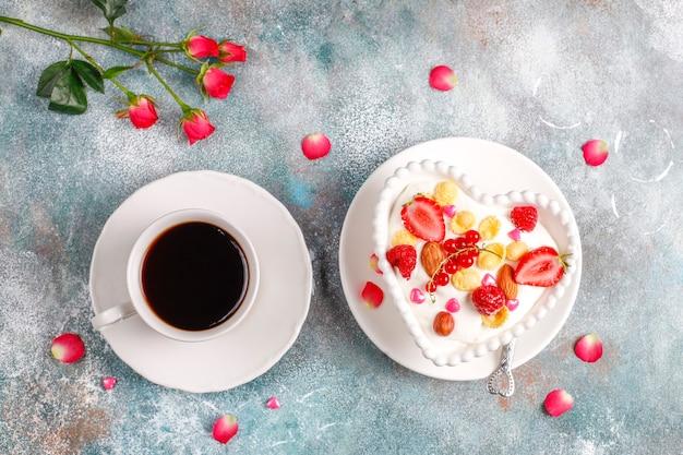 Yogur con hojuelas de maíz y frutos rojos en un tazón con forma de corazón.