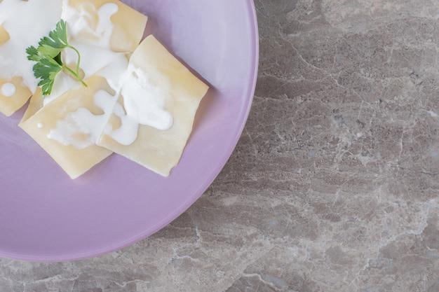 Yogur en láminas de lasaña con verduras en el plato, sobre el mármol.