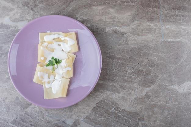 Yogur en láminas de lasaña con verduras en el plato, sobre la superficie de mármol.