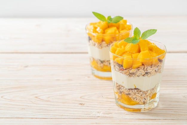 Yogur de mango fresco con granola en vidrio - estilo de comida saludable