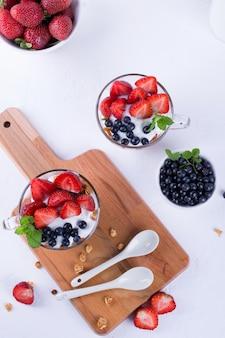 Yogur con muesli y bayas en pequeños vasos de vidrio. mesa de desayuno