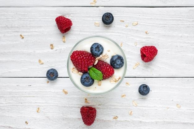 Yogur saludable con bayas frescas, avena y menta en un vaso en la mesa de madera blanca. desayuno saludable