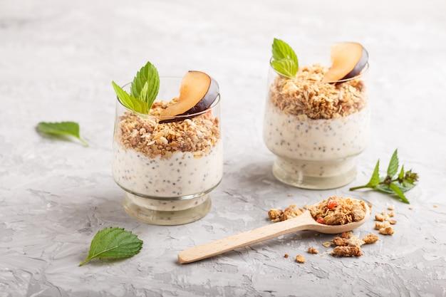 Yogur con semillas de ciruela chia y granola en un vaso y una cuchara de madera sobre fondo de hormigón gris
