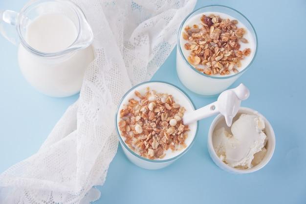Yogur en vaso, leche y queso crema en una mesa con servilleta blanca. vista superior.