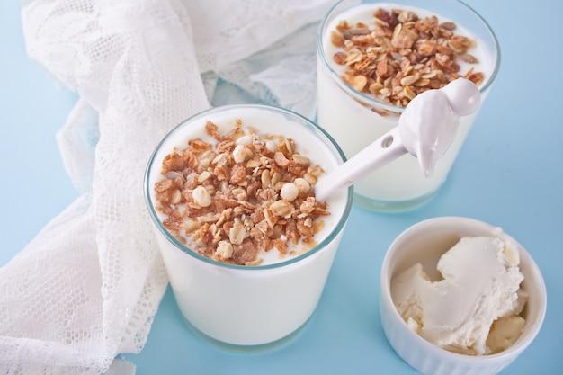 Yogur en vaso con muesli, queso crema en una mesa con servilleta blanca.