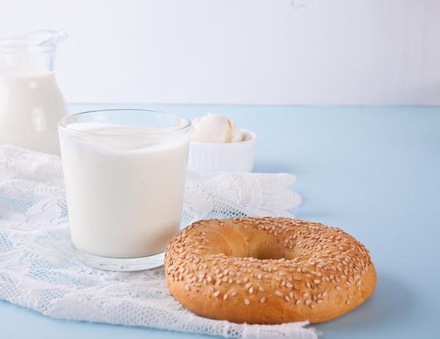 Yogur en vidrio y panecillo fresco en una mesa con servilleta blanca.