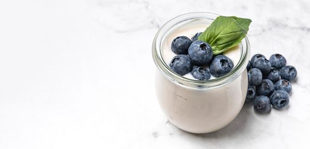 Yogurt de alto ángulo con arándanos y espacio de copia