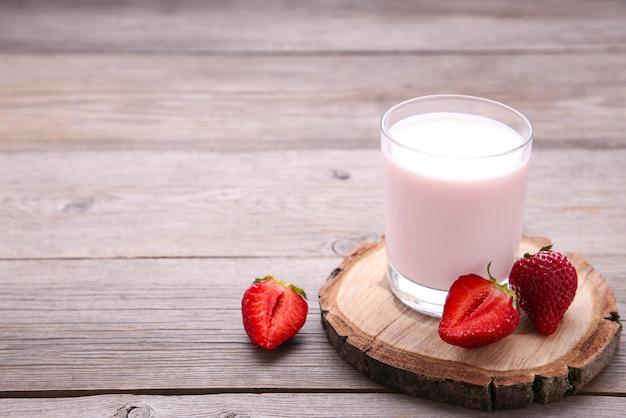 Yogurt con fresa en vaso sobre madera gris.