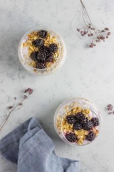 Yogurt con granola, semillas de chia y moras en un gris